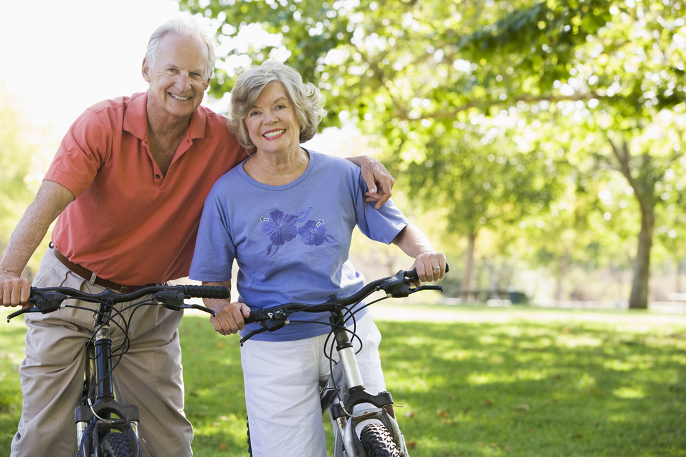 Happy elderly couple biking