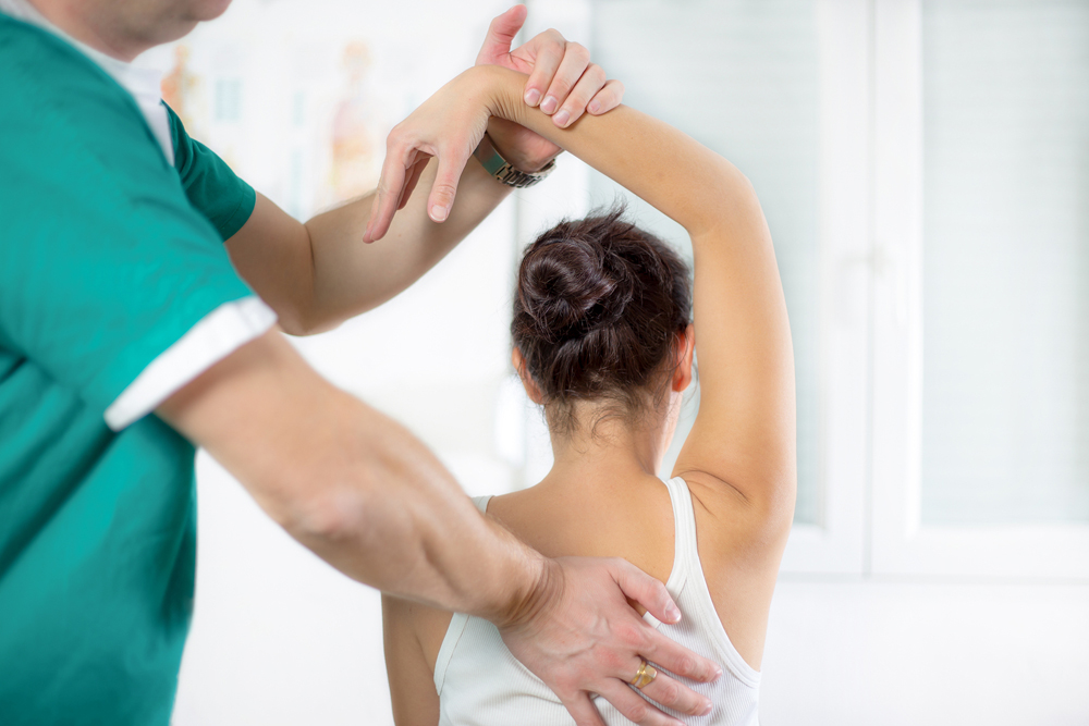 Woman with shoulder pain getting chiropractic care.